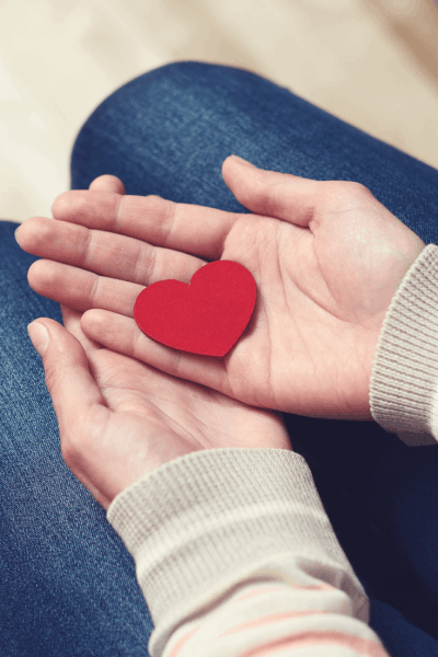 Manos con corazón de cartulina roja