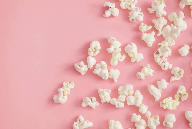 Palomitas de maíz sobre fondo rosa