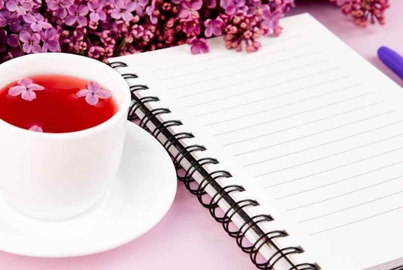 Cuaderno lineado con taza de té y flores