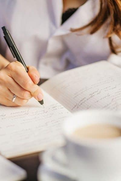 Mujer escribiendo diario con taza en la mesa