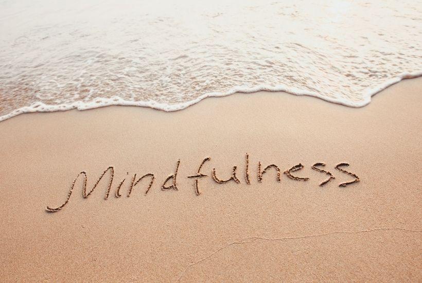 Palabra mindfulness escrito en arena