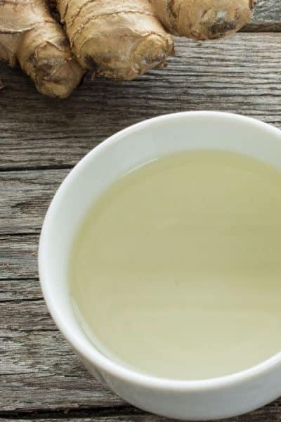 Trozo de jengibre y taza con té de jengibre